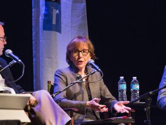 Prof. Susan Roberts sit in on an NPR panel, and speaks into a microphone while seated on stage