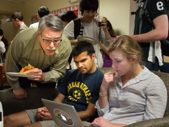 Prof. Neidinger at Pi Day celebration with students working on projects on laptops