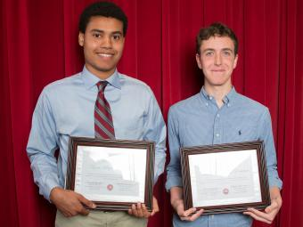 Two students stand in front of red curtain holding their economics awards
