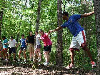 Students hold hands while standing on logs and try to complete a Davidson Outdoors challenge course