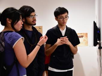 Three students huddle around art work displayed in the gallery and discuss