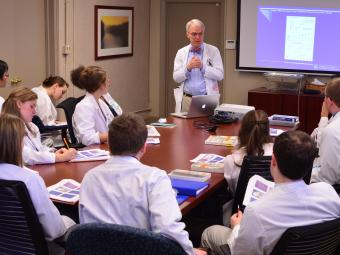 Students gather around a table at Carolinas Medical Center, listening to a lecture while they have a shadowing experience