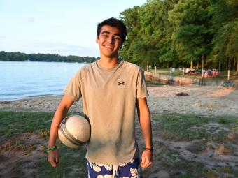 Student holds volleyball while standing in front of the lake access at Lake Campus