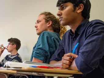 Three students sit at desk looking ahead during a political science class