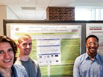 Three students stand around their research posters, ready to present