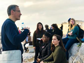 Prof. Randy Ingram speaks to class while holding a water bottle as students sit on a bench and on marble blocks at the Acropolis