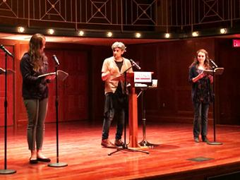 Professor stands on stage while three finalists for an award join him on stage reading from books they each hold
