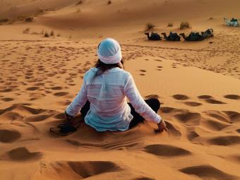 Student sits on sand hill surrounded by desert facing away from the camera.