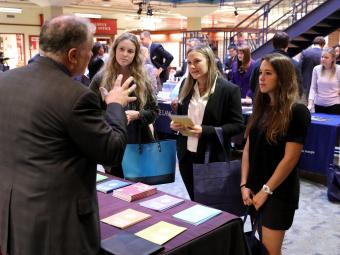 Three students visit a law school fair booth and recruiter talks to them
