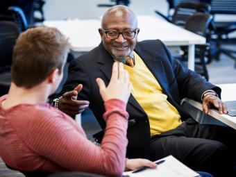 Robert Bullars smiles while a student sitting next to him discusses economics