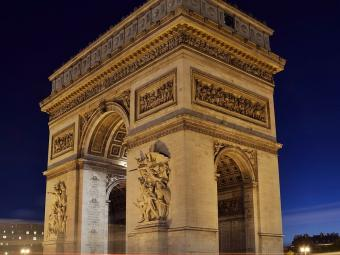 Arc de Triomphe at night with lights from cars as lines