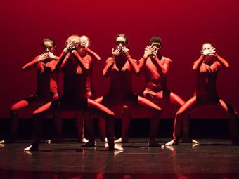 Group of students on stage pose together during a dance performance