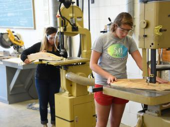 Two students work with machinery that cuts wood for a sculpture at the Sculpture Lab
