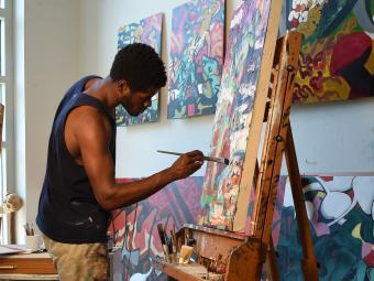 Student is painting a canvas in his studio at the Visual Arts Center
