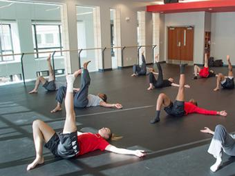 A large group of students in dance class lay on mats in the dance studio and hold their legs in the air