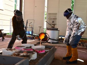 Professor and student dressed in protective gear pour liquid bronze at the bronze foundry.