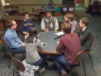 Professor and six students sit around a round table in the Union discussing economics