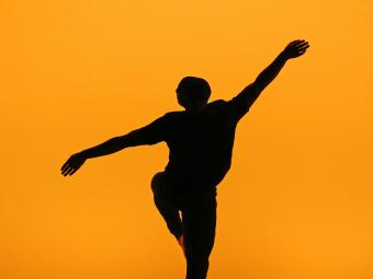 Student dances on stage and their silhouette is captured moving freely