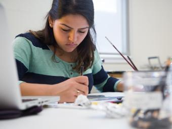Student sits at workstation painting, surrounded by art supplies