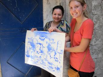 Student and Syrian artist hold watercolor painting.