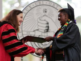 President Quillen and student shake hands at commencement
