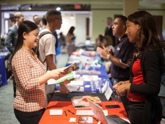 Recruiter talks to student at a booth at job fair