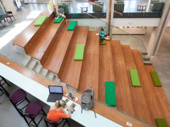 Wall Center wooden amphitheater including students who are studying on the steps