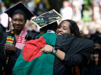 Graduating student hugs another student