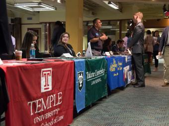Rows of booths are visible at the law school fair with students talking to recruiters