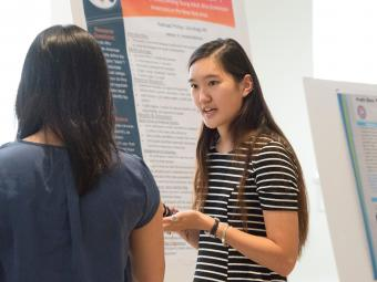 Student presents her poster research to an audience member
