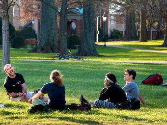 Students sit in a group on Chambers Lawn laughing