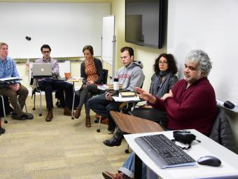 Arab studies class arranges desk in a circle while listening to a discussion led by Khaled Khalifa, a Syrian screenwriter and novelist