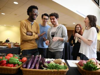 Students in commons with veggies for Cooking with Mamma demonstration
