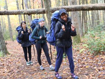 Three students backpacking in the woods walk in a line