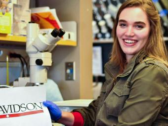 Student in lab at summer internship holds up a sign with the Davidson logo