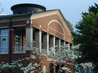 Belk Visual Arts Center exterior, framed by a dogwood tree and pink flowers
