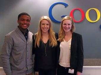 Three students stand in front of the Google sign during their internship