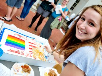 Student cuts a cake with a rainbow flag on it