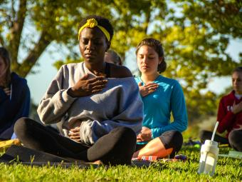 Group of students meditate outdoors