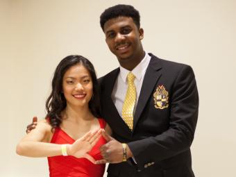 Two Students make Delta Sorority and Alpha Fraternity hand signs