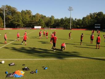Alumni Soccer Stadium field during a soccer team practice where team members are scattered across the field
