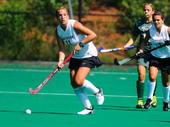 Field hockey game where two Davidson players and one competitor are running towards a ball