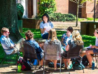 Student group sits on outdoor furniture by grassy area