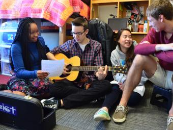 Students hang out in a dorm playing the guitar