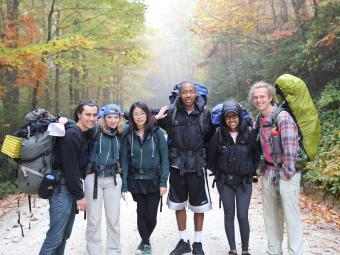 Students backpack with camping gear in the mountains with fall foliage