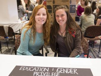Two students sit at booth with a poster focused at education and gender privilege