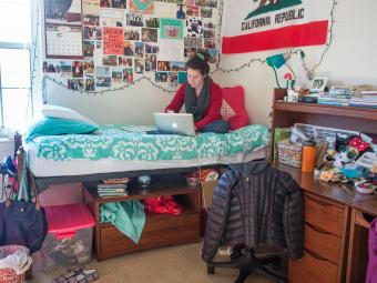Student sits on her dorm bed and looks at her laptop
