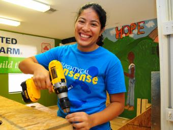 Volunteer holds a drill to plywood inside Habitat offices
