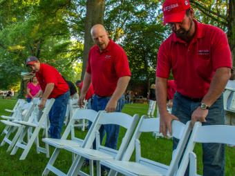 Physical Plant employees set up chairs for the Commencement ceremony