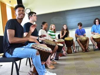 July Experience students drumming in big circle